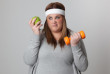 Annoyed woman holding and apple and a dumbbell.
