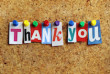 Thank you from cutout newspaper headlines pinned to a cork bulletin board