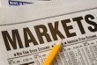 Newspaper open to market pages showing results.  Idea of studying the markets