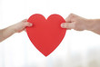 people, love, charity and family concept - close up of child and male hands holding red heart shape at home